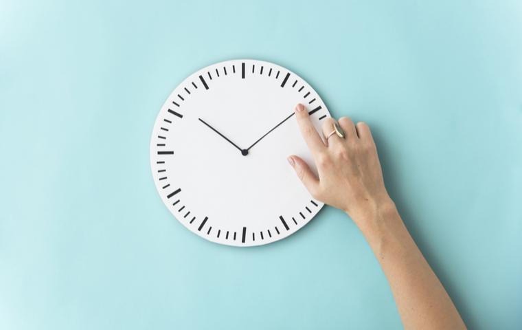 時計を指でさす