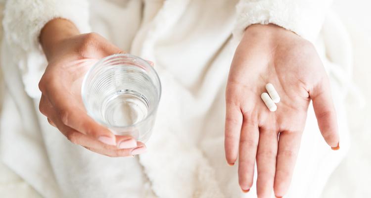 薬を手に持つ女性