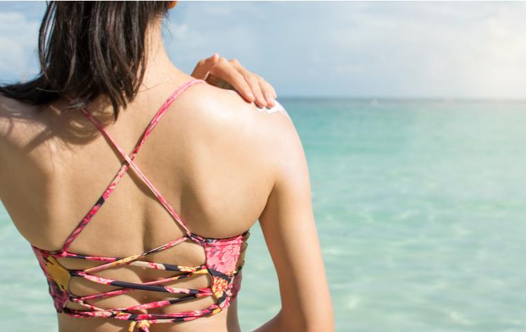 海辺で日焼け止めを塗る女性